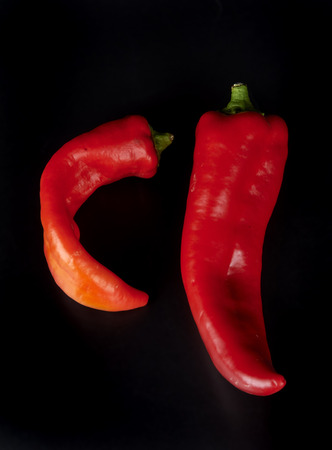 ailment: two  peppers on a black background Stock Photo