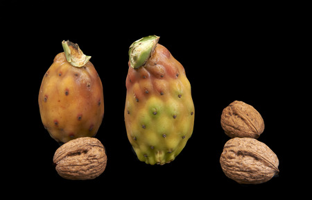 ailment: some  prickly pears and some walnuts on a black background