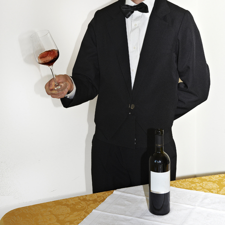 sommelier: a sommelier pours the wine into a glass