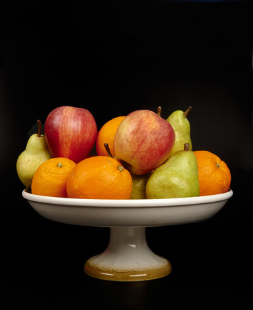 fruit bowl: a fruit bowl with oranges,apples and pears on the black background