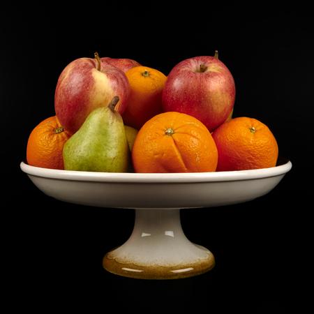 een fruitschaal met sinaasappelen, appels en peren op de zwarte achtergrond Stockfoto