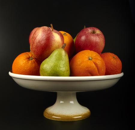 een fruitschaal met sinaasappelen, appels en peren op de zwarte achtergrond