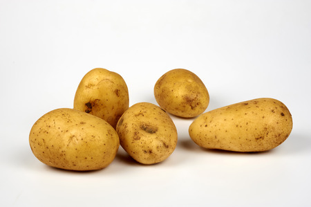 ailment: some organic potatoes on white background