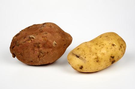 ailment: a sweet potato ( ipomoea batatas ) and a potato common( solanum tuberosum )  on white background Stock Photo