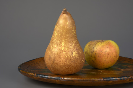 ailment: a pear and a apple on a plate on a gray background