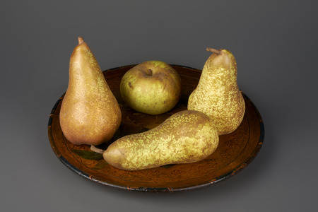 ailment: some pears and a apple on a plate on a gray background