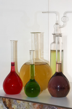 some glass bottles with colored liquid on a shelf