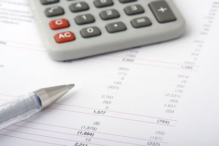 Business financial reports with pen and calculator Stock Photo