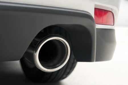 chrome exhaust pipe of a car with a tire in the back and a red light photo