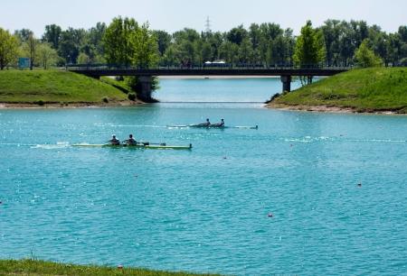 skiff: Race rowers on lake Jarun, bridge in back, Croatia