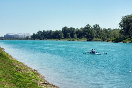 Two young men rowing on lake Jarun, arena Zagreb in back, Croatia