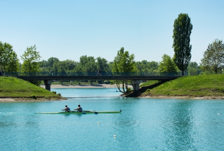 Two young men rowing on lake Jarun, bridge in back, Croatia