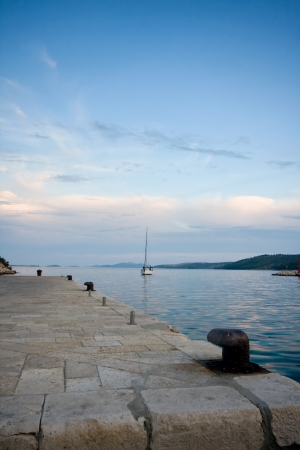 Some bollards and a sailing ship, Dugi otok Croatia Stock Photo