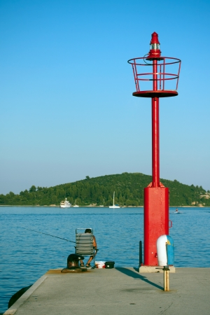 Red lighthouse and a fishing man Stock Photo