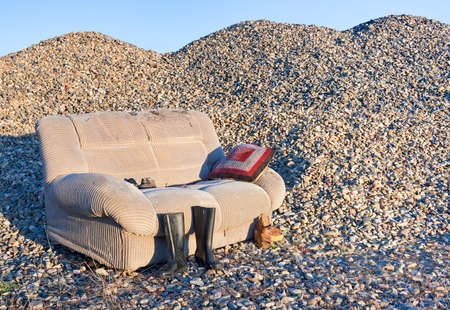 An abandoned sofa in a closed gravel pit that processed river stones. Foto de archivo