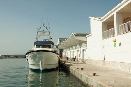 Fishing boat moored in the port of the fish market, ready to go fishing. Spain. 免版税图像