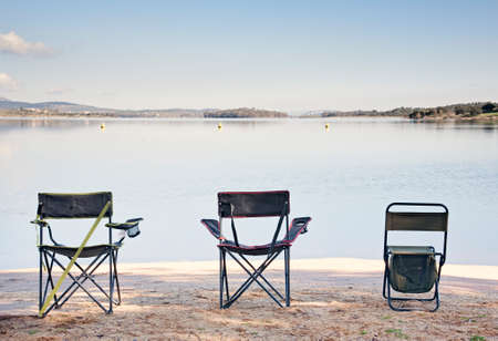 Beautiful couple landscape of a picturesque lake at sunrise with three chairs waiting to be used Banco de Imagens
