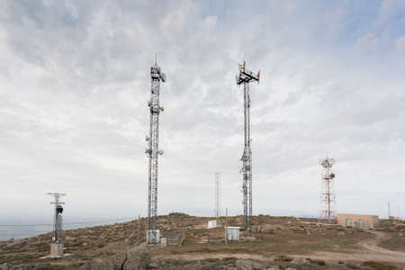 A communications center on top of a hill with large, tall antennas. Big Data.