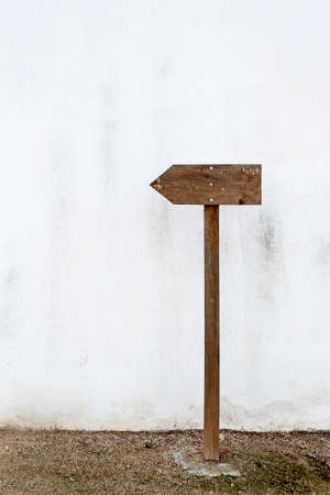 Empty wooden indication sign on a white wall