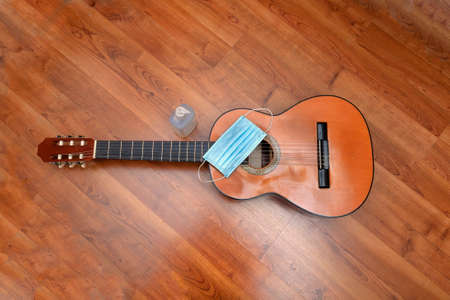 A surgical mask and an antiseptic dispenser next to a guitar to prevent to the coronavirus or covid-19 pandemic.