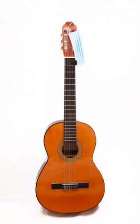 A surgical mask next to a Spanish guitar during the quarantine due to the coronavirus or covid-19 pandemic.