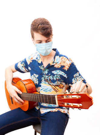 Young guy in a medical mask plays the guitar. Home entertainment in isolation.