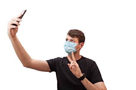 Young man wearing a face mask during the Coronavirus COVID-19 pandemic using his mobile phone to take a selfie.