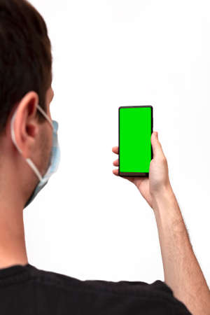 Young man wearing a face mask during the Coronavirus COVID-19 virus pandemic while checking his mobile phone.