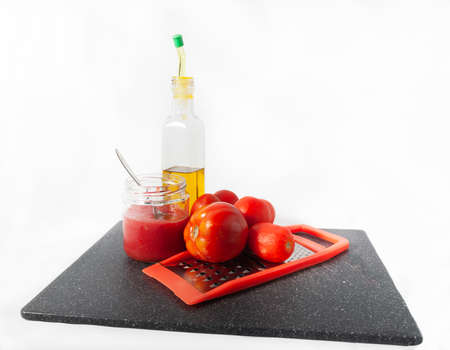 Preparing breakfast with oil and tomato juice with a metal grater 免版税图像