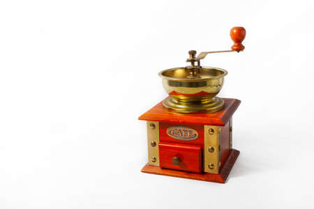 A golden brass and wood coffee grinder on a white background