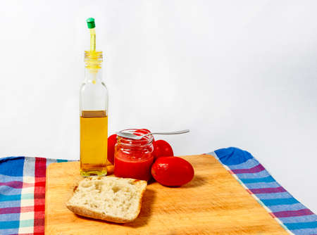 Preparing a toast of good bread, olive oil and tasty tomato juice on  white