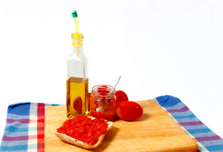 Preparing a toast of good bread, olive oil and tasty tomato juice on a white background.