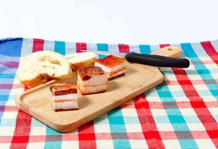 Three pieces of bacon on a cutting board on a white background.