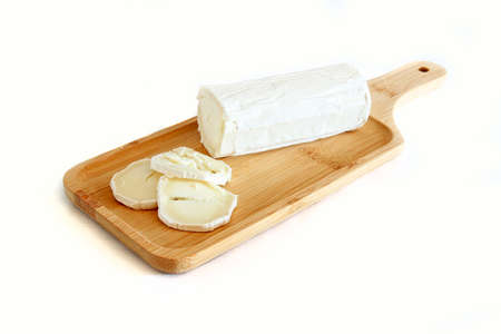 A tasty goat cheese roll atop a wooden cutting board over white background.