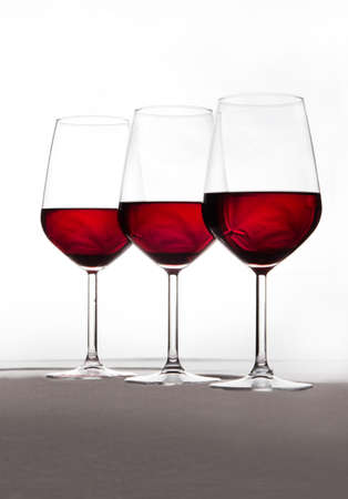 Three crystal glasses in harmony and full of wine on a white background.Drink
