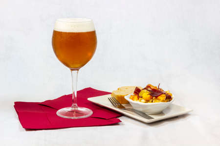 A cool beer served in a crystal glass along with a good appetizer of eggs with ham and bread on white background. 免版税图像