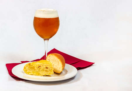 A cool beer served in a crystal glass along with a good piece of Spanish omelette with bread on white background 免版税图像
