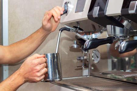 Professional barista holding metal jug warming milk using the coffee machine. Young man preparing coffee at counter. 免版税图像