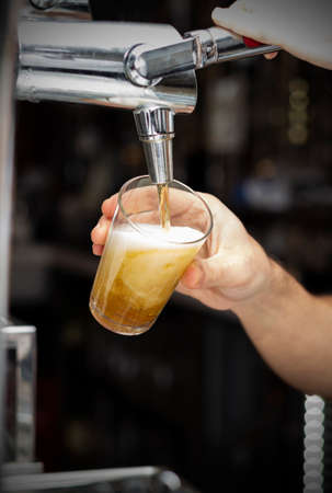 A bartender pouring draft beer into a glass