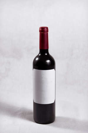 Bottle of dark red wine, red cap and white label without letters or marks