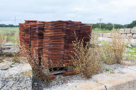 A pile of old rusty iron parts used in the construction and repair of the train tracks in a railway station.