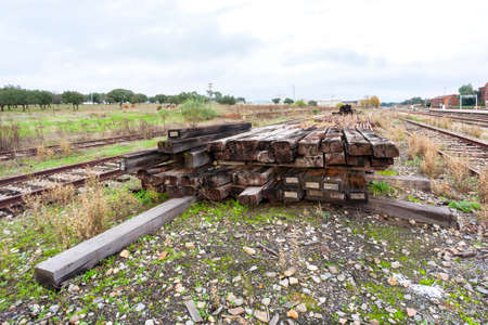 A pile of old timbers for the construction and repair of abandoned train tracks in a railway station. Train