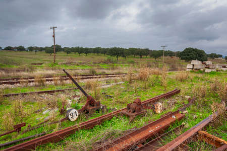 Several pieces related to the railroad, including a switchgear and several rusty iron rails of a train in a station. 免版税图像