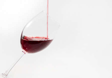 Red wine poured in a glass isolated on white.Drink