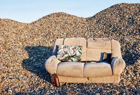 An abandoned sofa in a closed gravel pit that processed river stones. Outdoors
