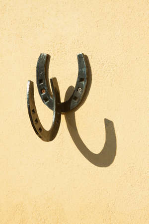 Hanging to leave clothes or bags made with two horseshoes welded together and nailed to the wall. Horses Standard-Bild