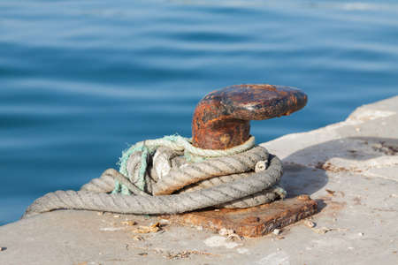 Iron pole for mooring of ships at pier, old rusty iron bollard on a pier on the coast of Andalucia, Spain. Landscape with sea wharf.