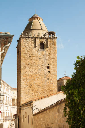Trujillo, Spain - November 18, 2012: Alfiler tower, a 14th Century Gothic belfry adorned with glazed roof tiles and favorite nesting place for storks, Trujillo, Spain