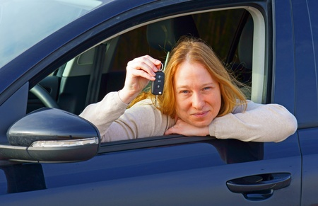 Woman in a car with car key photo