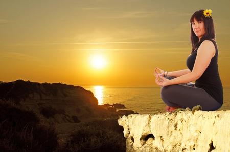 attractive sporty girl makes yoga in sunrise photo